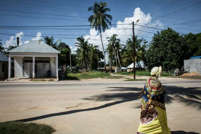 a person is walking down the street: Mozambique's authorities have insisted that Palma is now fully in government hands -- a claim widely disputed by analysts and sources on the ground