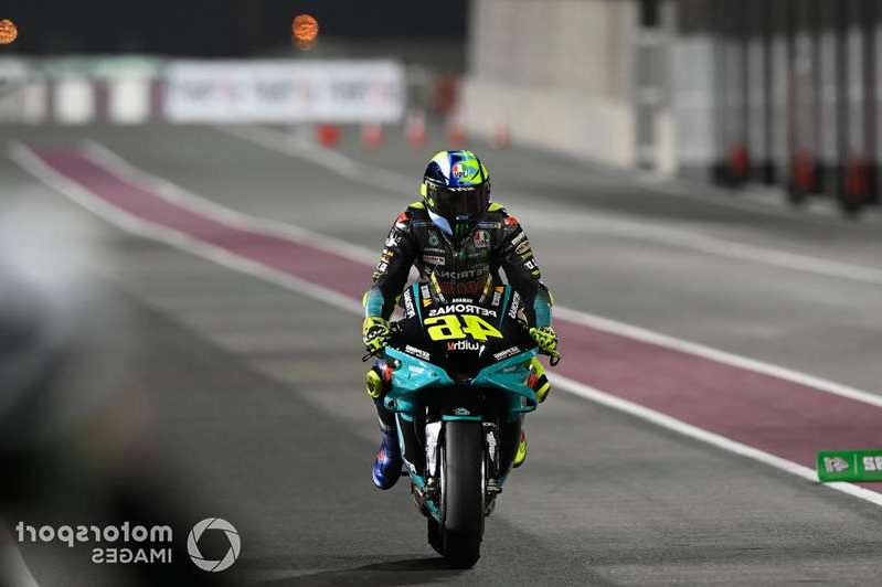 a person riding a motorcycle down a street: Valentino Rossi, Petronas Yamaha SRT