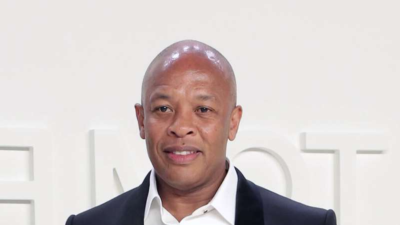 Dr. Dre wearing a suit and tie smiling at the camera
