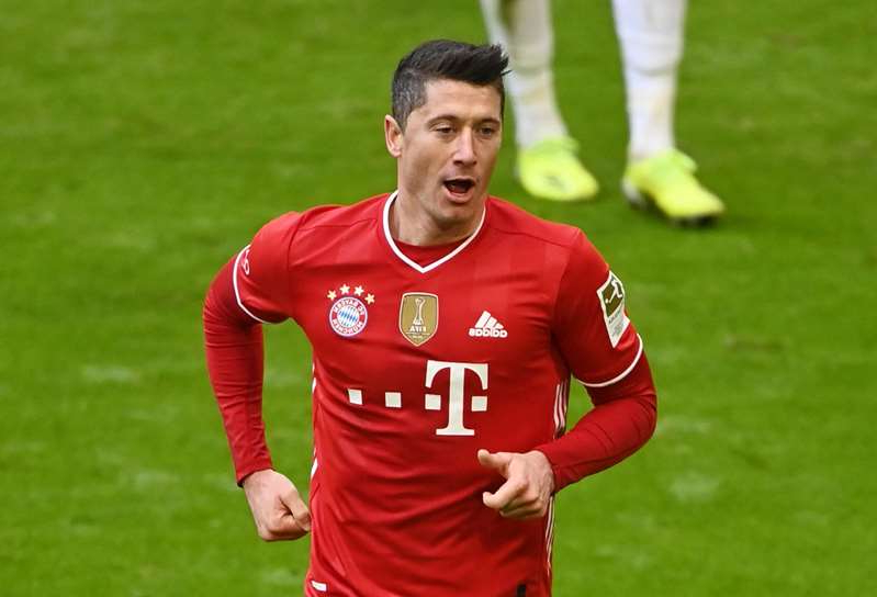 Robert Lewandowski holding a football ball on a field: FILE PHOTO: Bundesliga - Bayern Munich v VfB Stuttgart