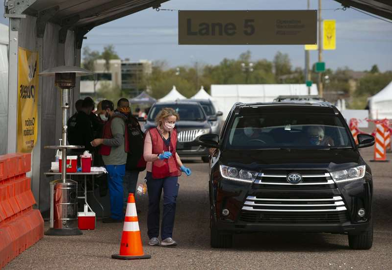 a group of people standing in front of a car: Dr. Cara Christ, director of the Arizona Department of Health Services, administers COVID-19 vaccines to educators in the parking lot at Phoenix Municipal Stadium on Feb. 1.