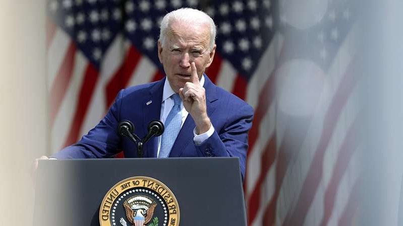 Joe Biden looking at the screen of a cell phone: Biden action on guns draws praise, skepticism