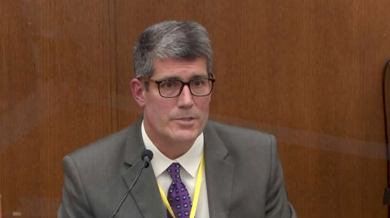 a man wearing a suit and tie: Dr. Andrew Baker of the Hennepin County Medical Examiner's Office testifies in the Derek Chauvin trial in Minneapolis on Friday. (Court TV via Reuters Video)