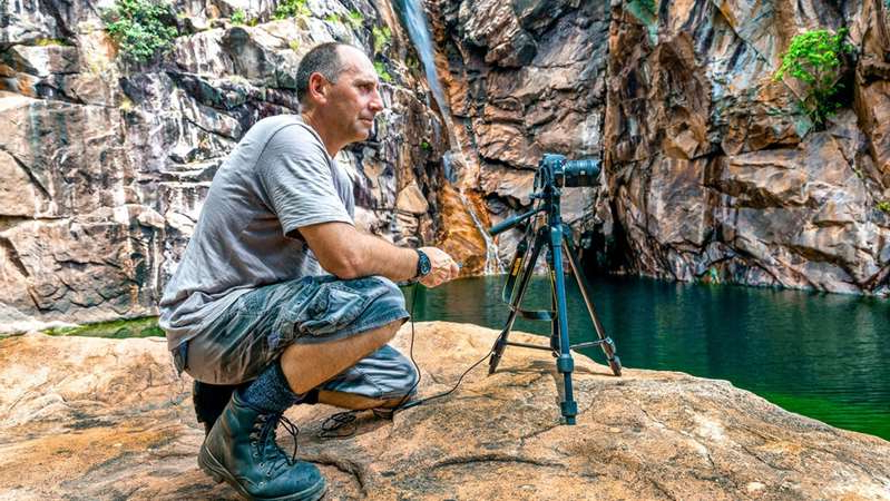 a man sitting on a rock: Jabiru resident Peter Keepence has spent years photographing heritage-listed Kakadu National Park, but he feels uncertain about its future. (Supplied: Peter Keepence)