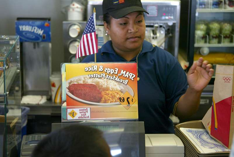 a boy sitting at a table in front of a store: A cashier rings up a sale as the McDonald's new Spam, Eggs and Rice Breakfast Platter is advertised June 11, 2002 in Wahiawa, Hawaii. (Getty Images)
