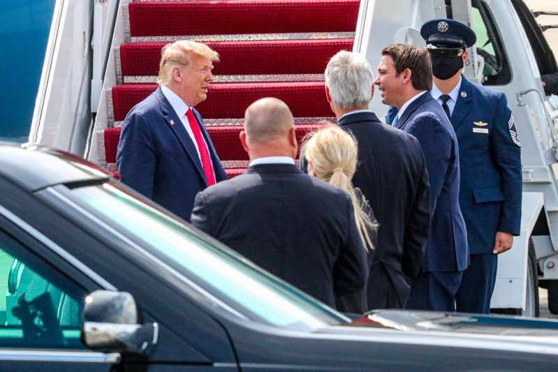 a group of people in a car: President Donald Trump arrives at Southwest Florida International Airport and deplaned at PrivateSky. Governor Ron DeSantis and Fort Myers Mayor Randy Henderson were among the small group welcoming the President.