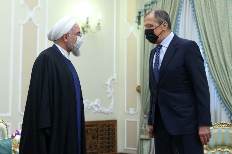 a man in a suit standing in front of a curtain: Russian Foreign Minister Sergei Lavrov is received by Iranian President Hassan Rouhani as he puts on a united front with his hosts on bringing the United States back into a troubled 2015 nuclear deal