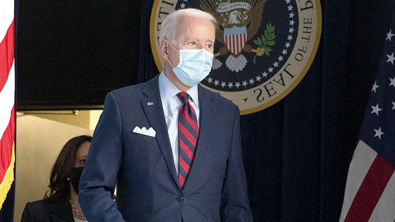 a man wearing a suit and tie: President Biden