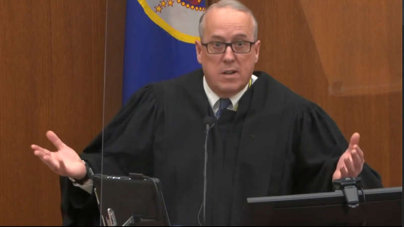 a person standing in front of a microphone: In this image from video, Hennepin County Judge Peter Cahill discusses motions before the court Tuesday, April 6, 2021, in the trial of former Minneapolis police Officer Derek Chauvin, in the May 25, 2020, death of George Floyd at the Hennepin County Courthouse in Minneapolis, Minn.