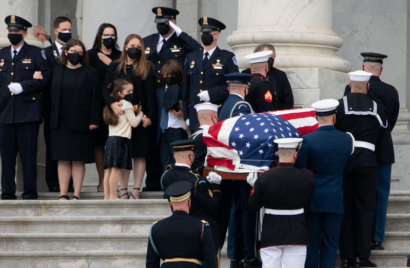 a group of people in uniform: Logan and Abigail Evans stand with their mother and grandmother while William Evans' casket is carried into the Capitol Rotunda. (Saul Loeb / AFP via Getty Images)