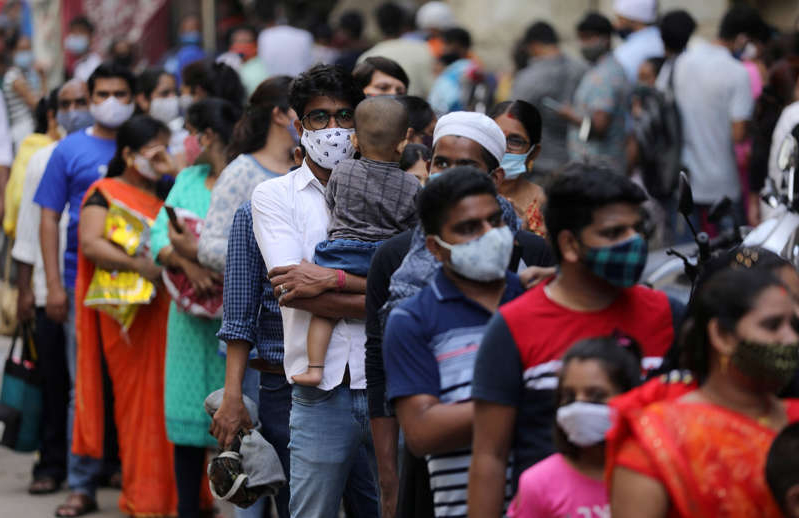 a group of people standing in front of a crowd: People wait in a line to enter a supermarket amid the spread of the coronavirus in Mumbai [File: Francis Mascarenhas/Reuters]