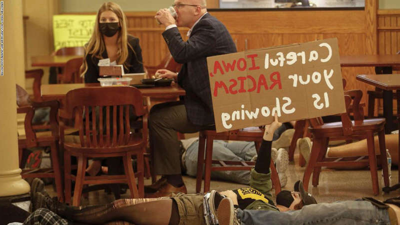 a person sitting at a table: Ayla Boylen of Cedar Rapids holds a protest sign as legislators have lunch during a Kill the Racist Bills protest at the Iowa Capitol Building in Des Moines on Thursday, April 8, 2021.  20210408 Protest