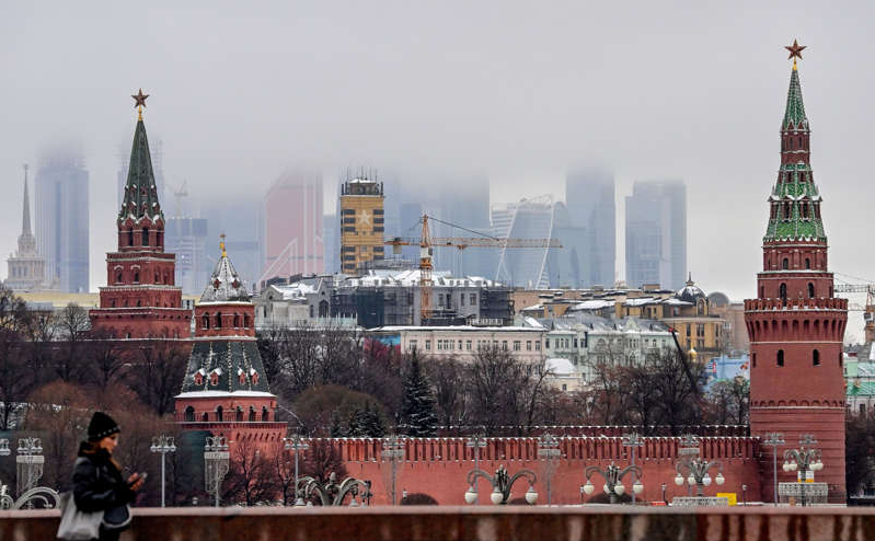a group of people standing in front of a tall building: The Kremlin and skyscrapers of the Moscow International Business Centre are pictured ) in Moscow on December 17, 2020. Russia faces U.S. sanctions over the Solar Winds hack which the Kremlin denies responsibility for.