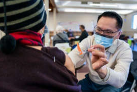 a man and a woman looking at her cell phone: Dr. E. Kwok administers a COVID-19 vaccine at a vaccination clinic run by Vancouver Coastal Health, in Richmond, B.C., on Saturday.