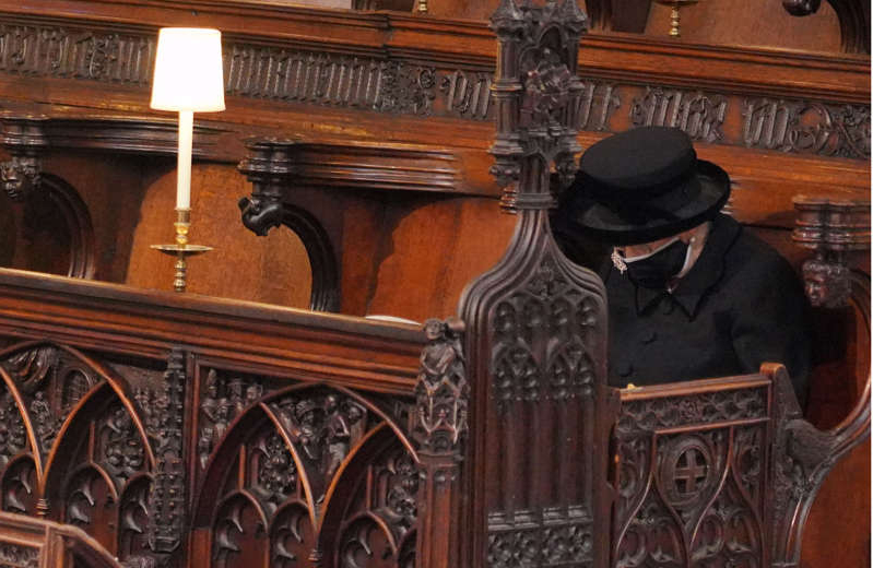 a clock on top of a wooden chair: Queen Elizabeth II sits alone at the funeral service of Britain's Prince Philip, Duke of Edinburgh inside St George's Chapel in Windsor Castle on April 17, 2021. Only 30 guests were permitted due to coronavirus restrictions.