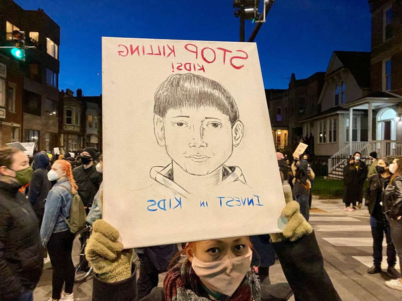 a group of people walking down a street next to a sign: A protester in Chicago holds up a drawing showing solidarity and support for Adam Toledo, 13, who died after being shot by police in an alley. A police bodycam video shows Adam had his hands up when he was shot.