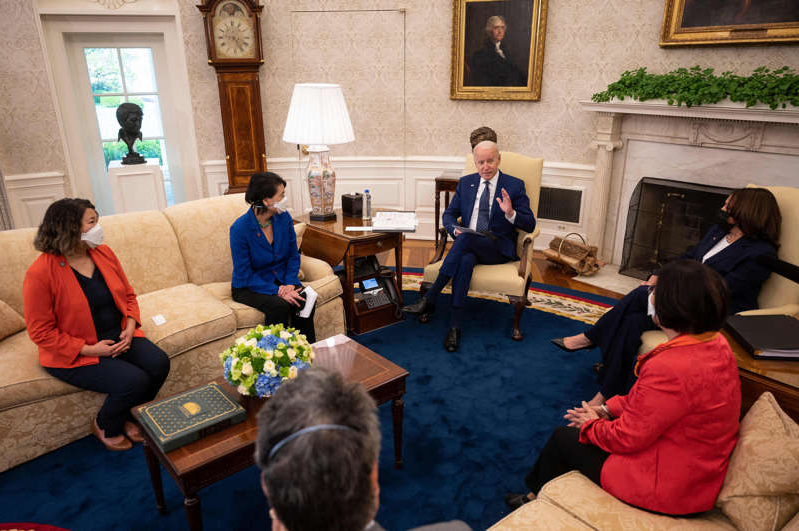 Joe Biden et al. sitting around a living room: US President Joe Biden (centre R) and Vice President Kamala Harris (L) meet with the Congressional Asian Pacific American Caucus Executive Committee at the White House in Washington, DC, on April 15, 2021.