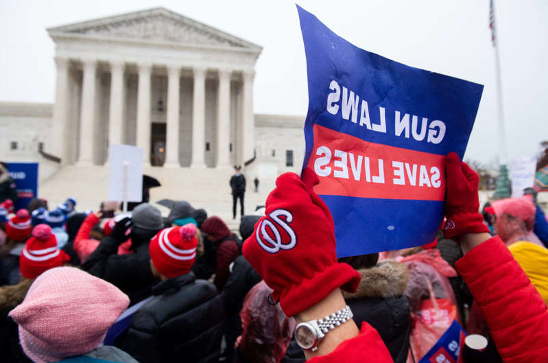 a group of people standing in front of a crowd: Supporters of gun control and firearm safety measures hold a protest rally outside the US Supreme Court as the Court hears oral arguments in State Rifle and Pistol v. City of New York, NY, in Washington, DC, December 2, 2019. - The case marks the first time in nearly 10 years that the Supreme Court has heard a Second Amendment gun ownership case. (Photo by SAUL LOEB / AFP) (Photo by SAUL LOEB/AFP via Getty Images) ORIG FILE ID: AFP_1MR16C