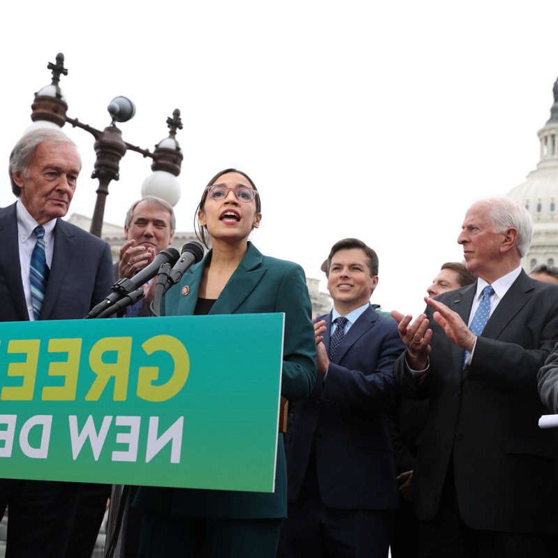 Brendan Boyle, Jeff Merkley, Ed Markey standing in front of a crowd posing for the camera: U.S. Representative Ocasio-Cortez and Senator Markey hold a news conference for their proposed