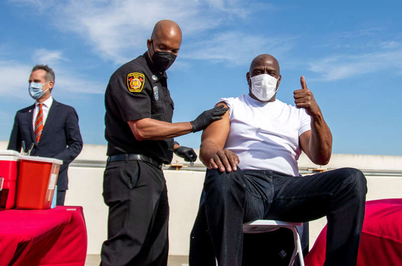 a group of people sitting in a chair talking on a cell phone: Magic Johnson (left) gives a thumbs-up after getting a vaccine last month, as a part of a vaccination awareness event at USC, in Los Angeles.