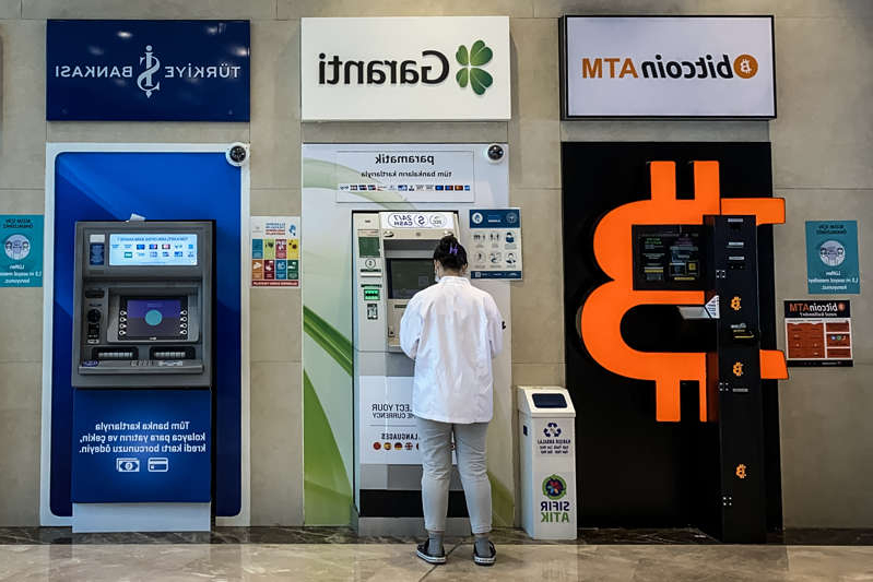 The founder of Thodex, a cryptocurrency exchange in Turkey, has been accused of fleeing the country with billions of dollars in investors assets. Here, a woman uses a bank ATM next to a Bitcoin ATM machine at a shopping mall on April 16, 2021 in Istanbul, Turkey.