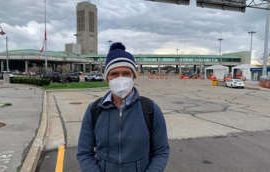a man that is standing in the street: Greg Peacock of Toronto walked across the Rainbow Bridge in Niagara Falls, Ont., into Canada on the morning of April 15 after flying from Los Angeles to Buffalo, N.Y. He's been using the land crossing instead of flying directly to Toronto to avoid the quarantine hotel stay that is mandatory for air travellers.