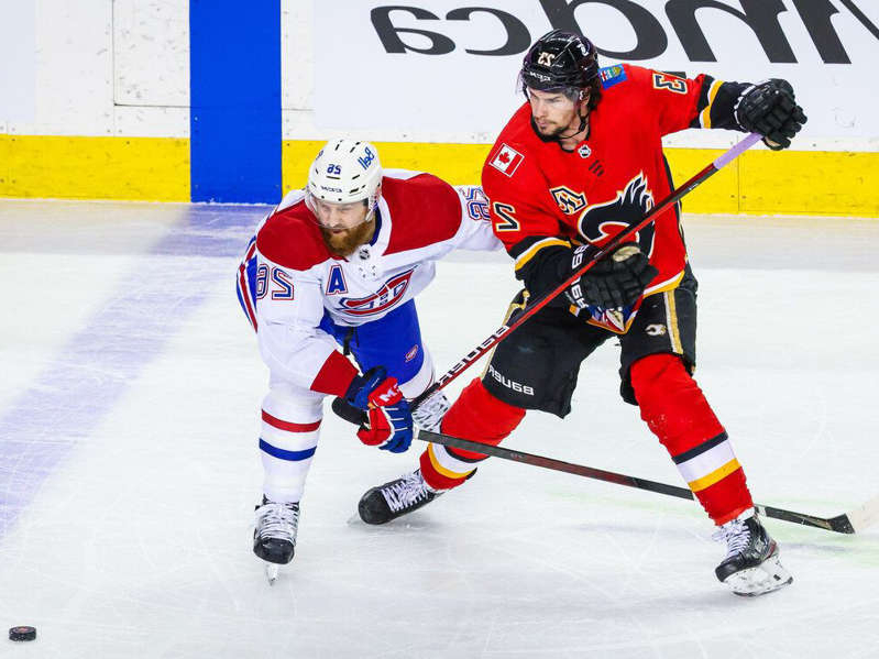 a hockey game in the snow: Flames' Sean Monahan (23) and Canadiens defenceman Jeff Petry battle for the puck during the first period at Scotiabank Saddledome in Calgary on Saturday, April 24, 2021.