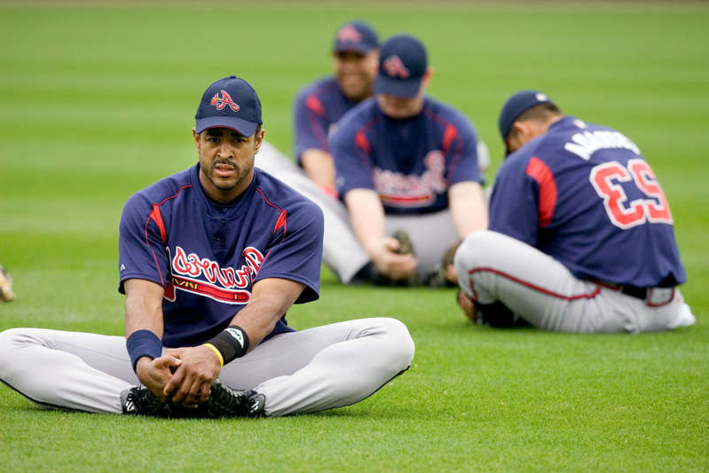 a baseball player holding a bat on a field: Atlanta Braves' Brian Jordan, right, stretches out at the beginning of workouts Tuesday, Feb. 22, 2005, at Cracker Jack Stadium in Kissimmee, Fla. (AP Photo/Scott Audette) ORG XMIT: FLSA105