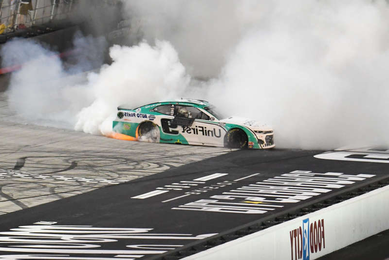 a train on a track with smoke coming out of it: Chase Elliott (9) does a burnout after winning the 2020 All-Star Race at Bristol Motor Speedway.