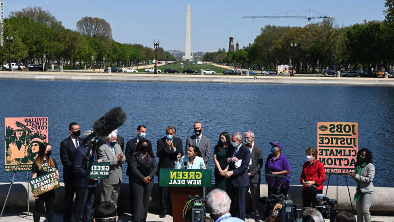 a group of people standing in front of a lake: Representative Alexandria Ocasio-Cortez(D-NY) next to Senator Ed Markey, D-MA, speaks during a press conference to re-introduce the Green New Deal in front of the US Capitol in Washington, DC on April 20, 2021.