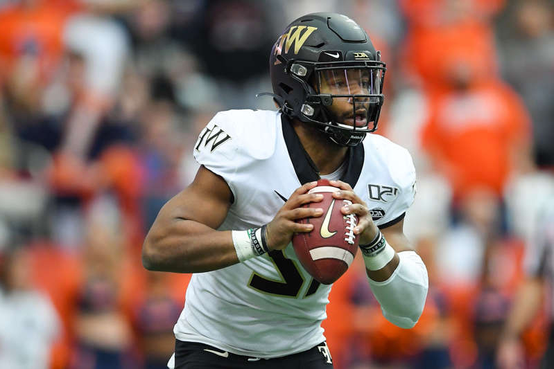 a close up of a baseball player holding a bat: Wake Forest Demon Deacons quarterback Jamie Newman (12) runs with the ball against the Syracuse Orange during the first quarter at the Carrier Dome.