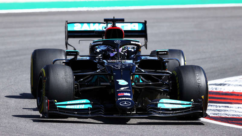 a motorcycle is parked on the side of a road: Lewis Hamilton at the Portuguese Grand Prix