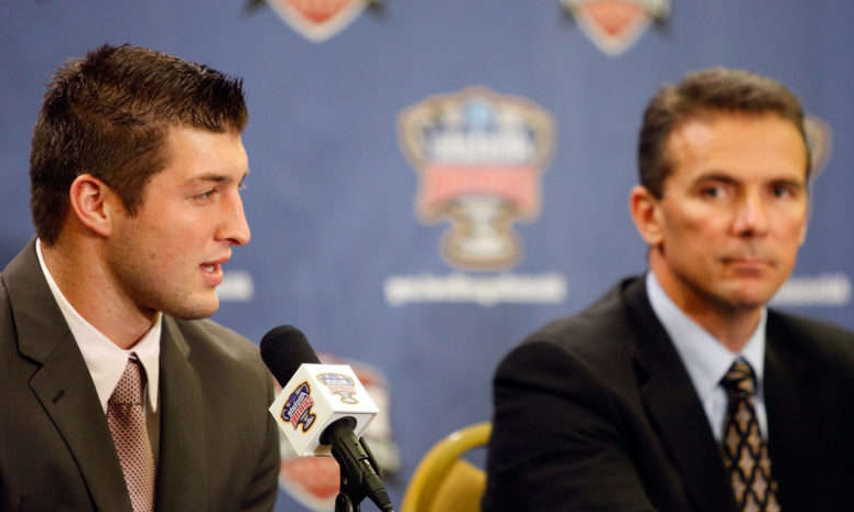 Urban Meyer, Tim Tebow are posing for a picture: Tim Tebow speaking at a press conference with Urban Meyer by his side.
