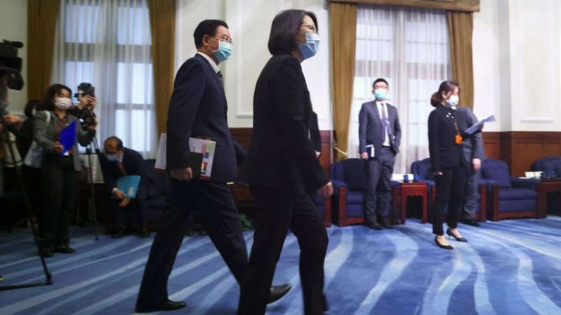 a group of people standing in a room: Will Biden provide strategic clarity or further ambiguity on Taiwan?