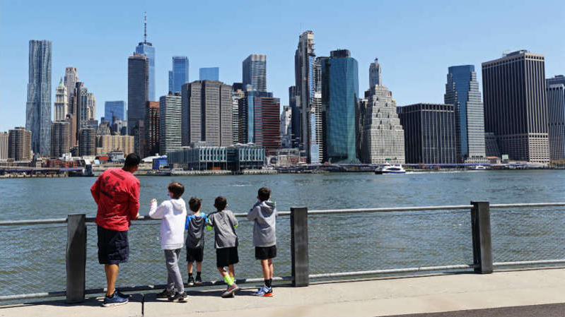 a group of people standing next to a body of water in a city: NYC public schools nix 'snow days' for remote learning