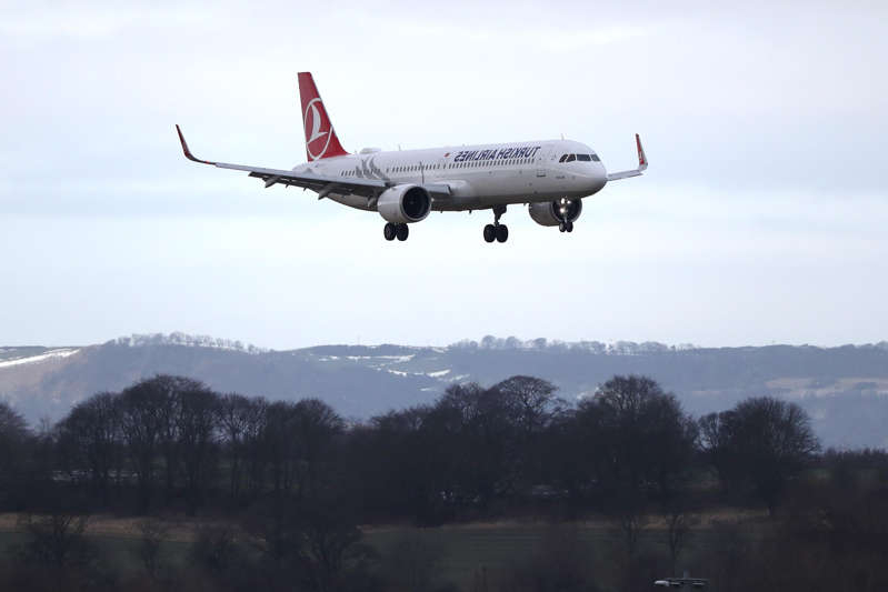 a large passenger jet flying through the air: A Turkish Airlines plane arrives at Edinburgh airport (PA)