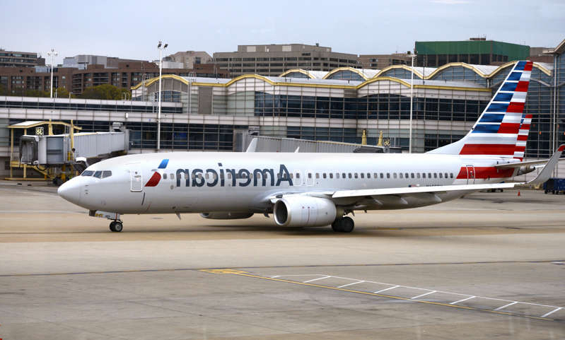 a large passenger jet sitting on top of a runway: File photo: An American Airlines Boeing 737 passenger plane taxis from a gate to the runway at Ronald Reagan Washington National Airport in Washington, D.C. A North Carolina woman said she was made to pay an