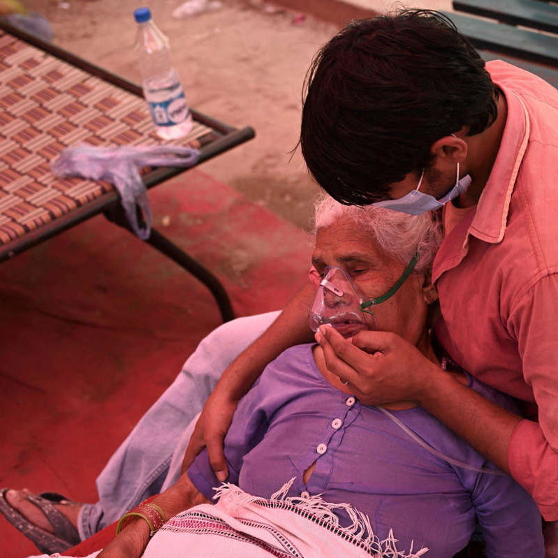 a man and a woman sitting on a bench: INDIA-HEALTH-VIRUS-OXYGEN