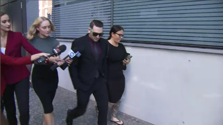 a man and a woman standing next to a window: Jonathan Lawrence outside of Brisbane Court today.