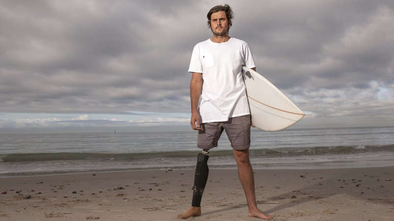 a man standing on a beach holding a surf board: Chris Bowes, 32, lost his leg when a great white shark attacked him in 2015