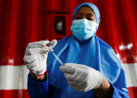 a person in a blue uniform holding a gun: A healthcare worker prepares a dose of China's Sinovac Biotech vaccine for the coronavirus disease (COVID-19) at a drive-thru vaccination station, as a mass vaccination program continues in Jakarta, Indonesia, April 30, 2021. It's an inactivated vaccine being used in countries around the world, but not in Canada.