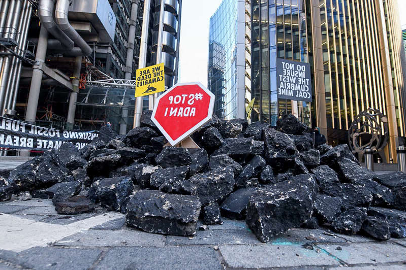 a stop sign on the side of a building: Protesters have previously demanded that the City stop financing coal (Insurance Rebellion/PA)