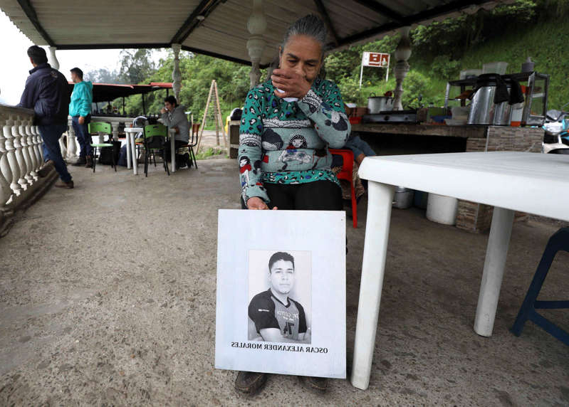 Doris Tejada, mother of Oscar Alexander Morales who disappeared on New Year's eve 2007, holds a photo of her son, at a shop in Soacha, Colombia, Thursday, April 8, 2021. Tejada and her husband found out that their son indeed is on the list of the