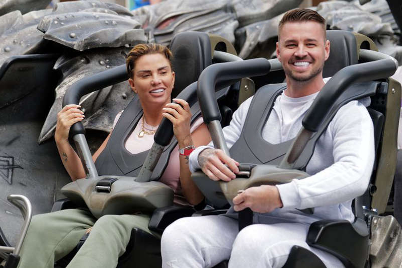 Katie Price et al. sitting around a car: Katie Price and Carl Woods were seen beaming as they enjoyed a childfree day at Thorpe Park