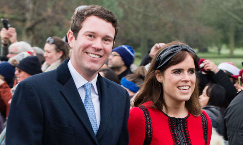 Princess Eugenie of York wearing a suit and tie standing in front of a crowd: Hello! Magazine
