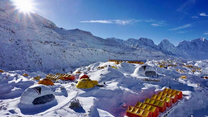 a group of people sitting on top of a snow covered mountain: Health officials have warned of rising numbers of Covid-19 cases at base camp