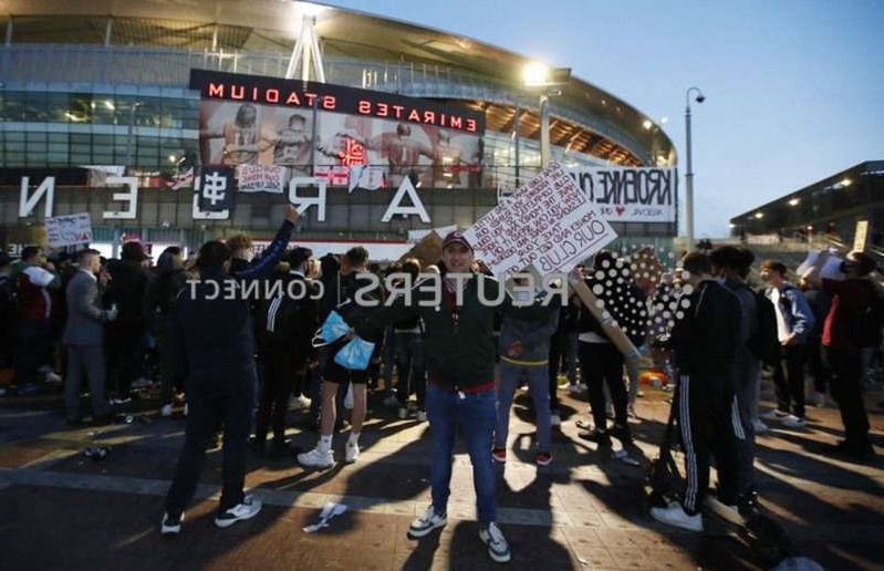 a group of people standing in front of a building: Arsenal fans protest against owners KSE and Stan Kroenke's involvement in the European Super League