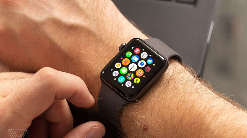 a hand holding a remote control: Apple Watch