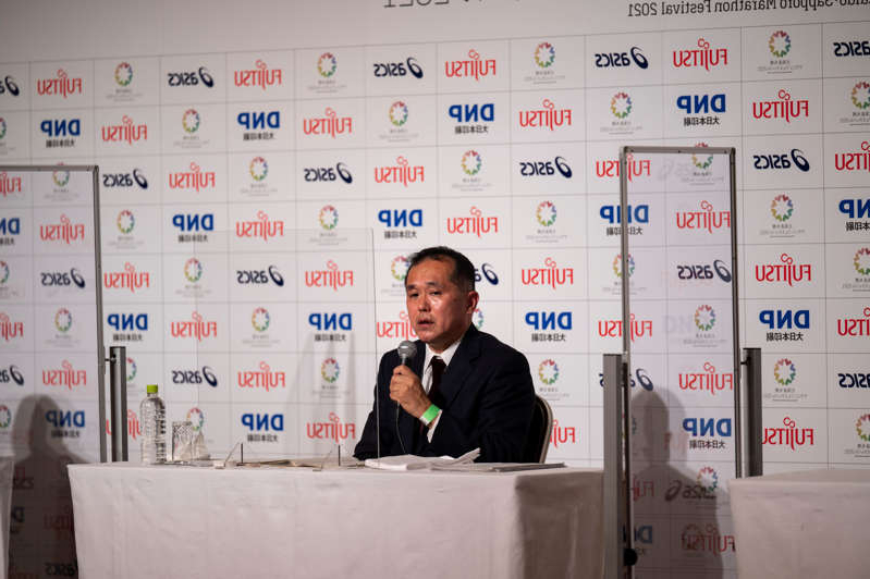 a man sitting on a table: News conference prior of the half-marathon race which doubles as a test event for the 2020 Tokyo Olympics