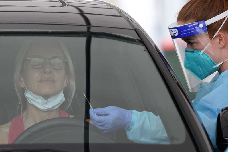 a person wearing a hat and sunglasses: FILE PHOTO: A medical worker swabs a member of the public at a drive-through COVID-19 testing centre in Sydney